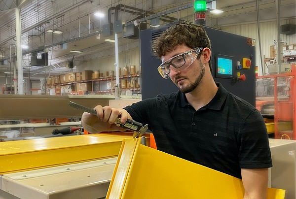 Employee working with a large plastic profile