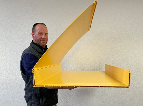 Employee holding a sample of a large plastic extruded profile